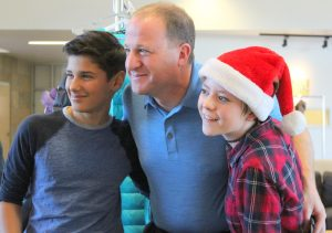 Two young audience members pose with Representative Polis after the town hall.